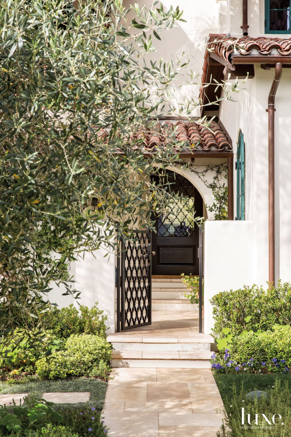Traditional Cream Entry with Arched-Doorway and Olive Tree