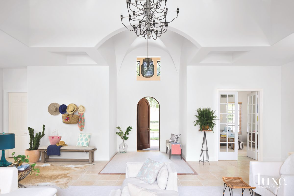 White Entrance Living Room with Chandelier and Coat Rack