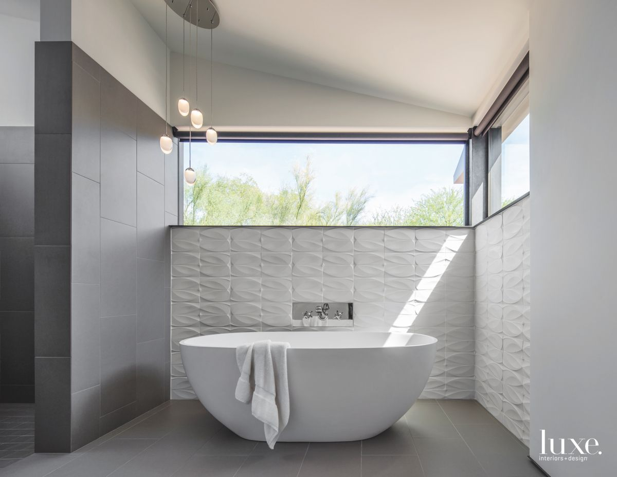 Repeated White Tile Bathroom Walls with Large Soaking Tub and High Windows