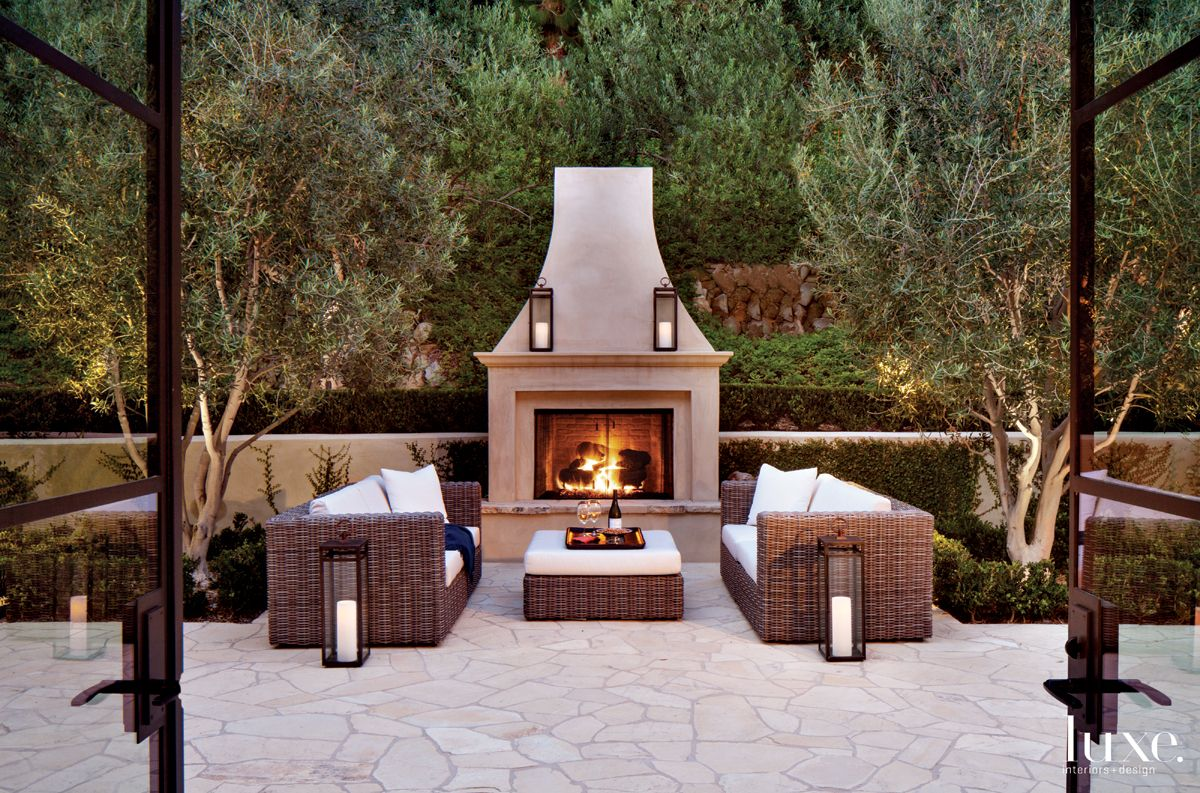 Country Neutral Outdoor Seating Area with Limestone Fireplace