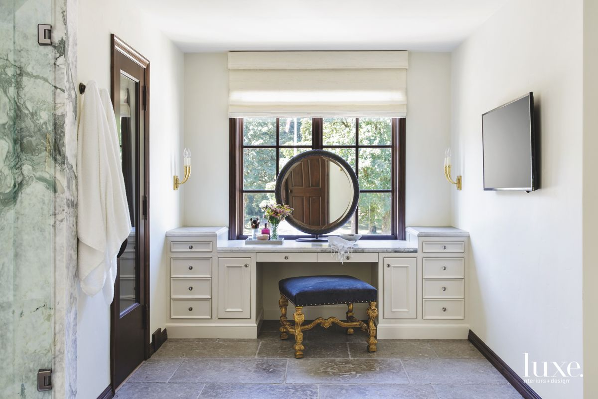 Master Bedroom Vanity with Circular Mirror, White Cabinetry, and Antique Stool