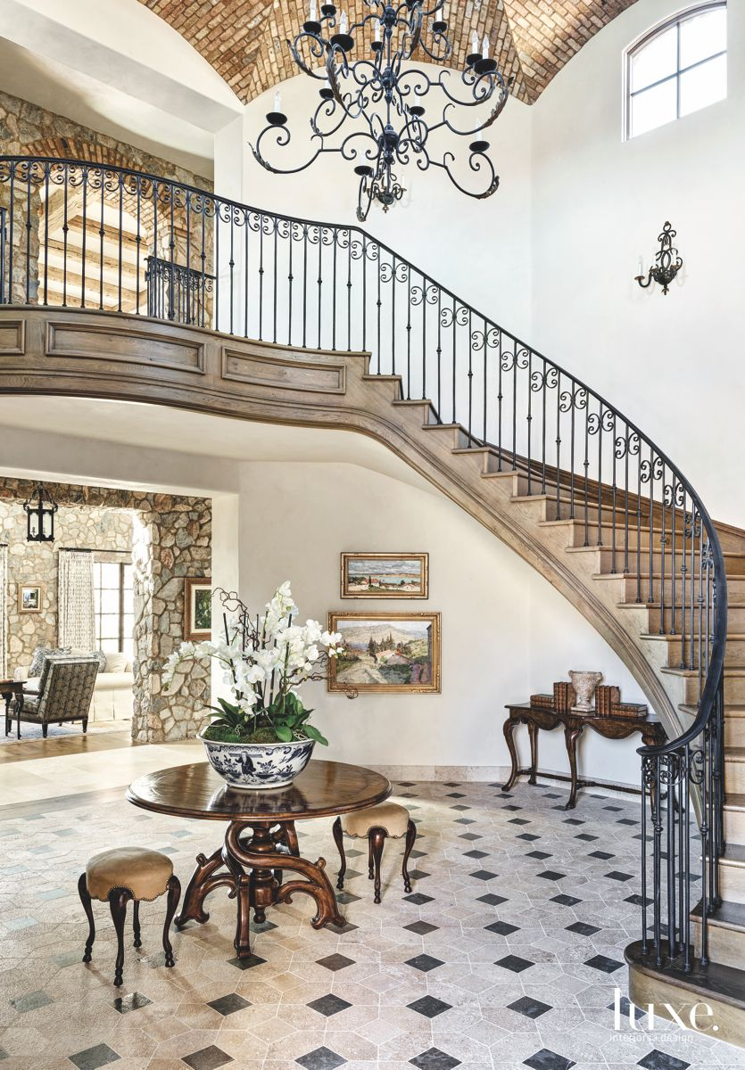Brick Vaulted Ceiling Staircase with Traditional Black Iron Chandelier and Art