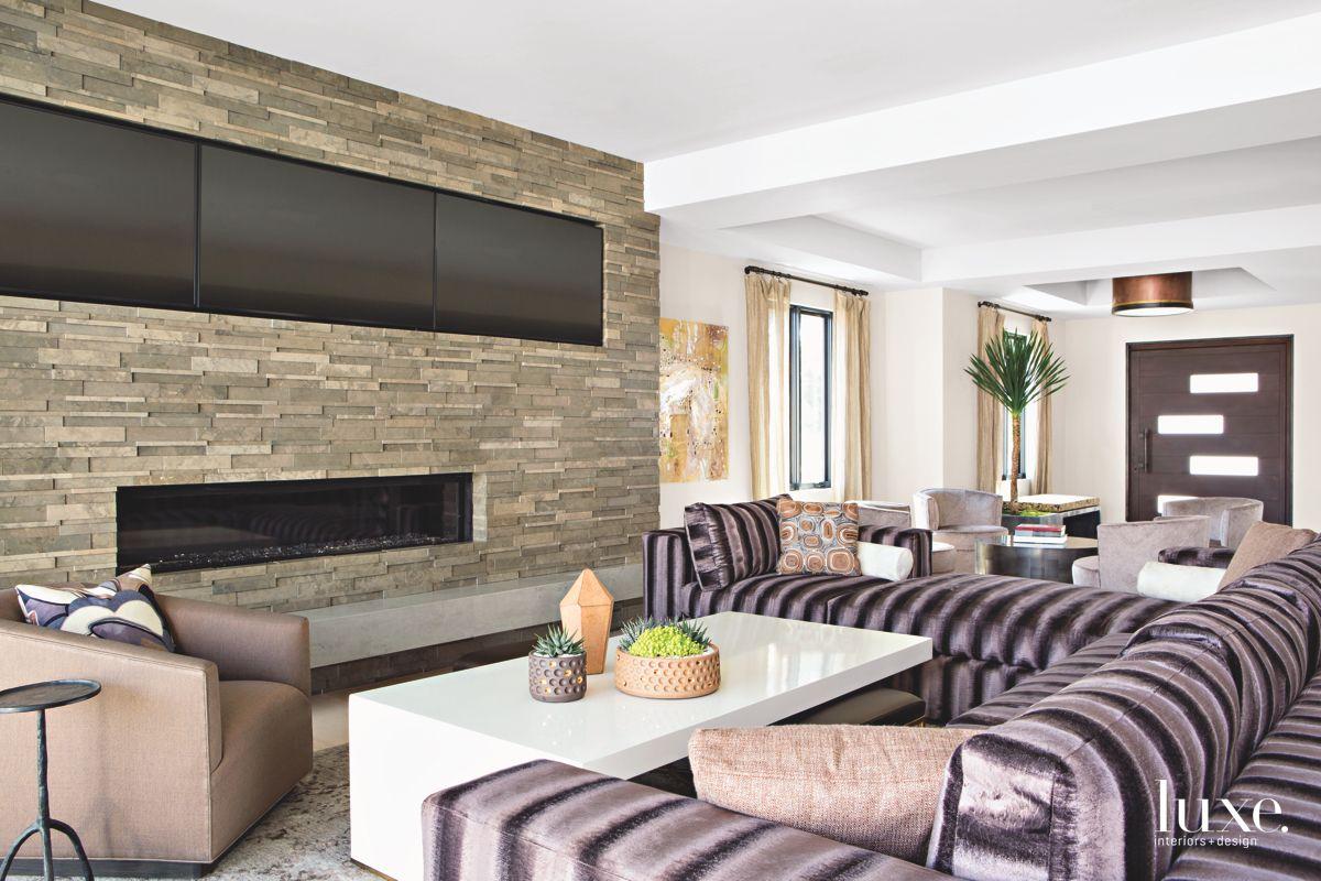Three Flat-Screen TVs Atop a Stone Fireplace