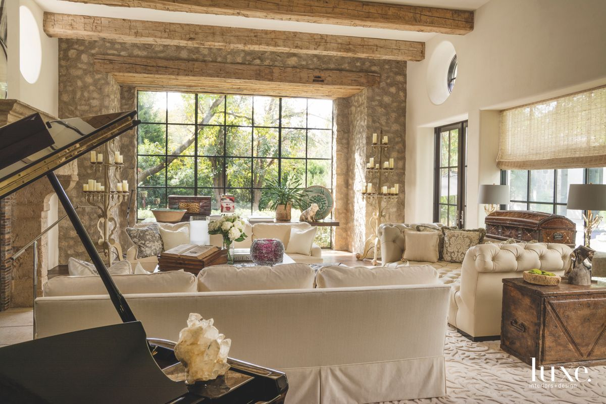 Neutral Beige Living Room with Reclaimed Wood Beam Ceiling, Piano, Stone Wall, and Antiques