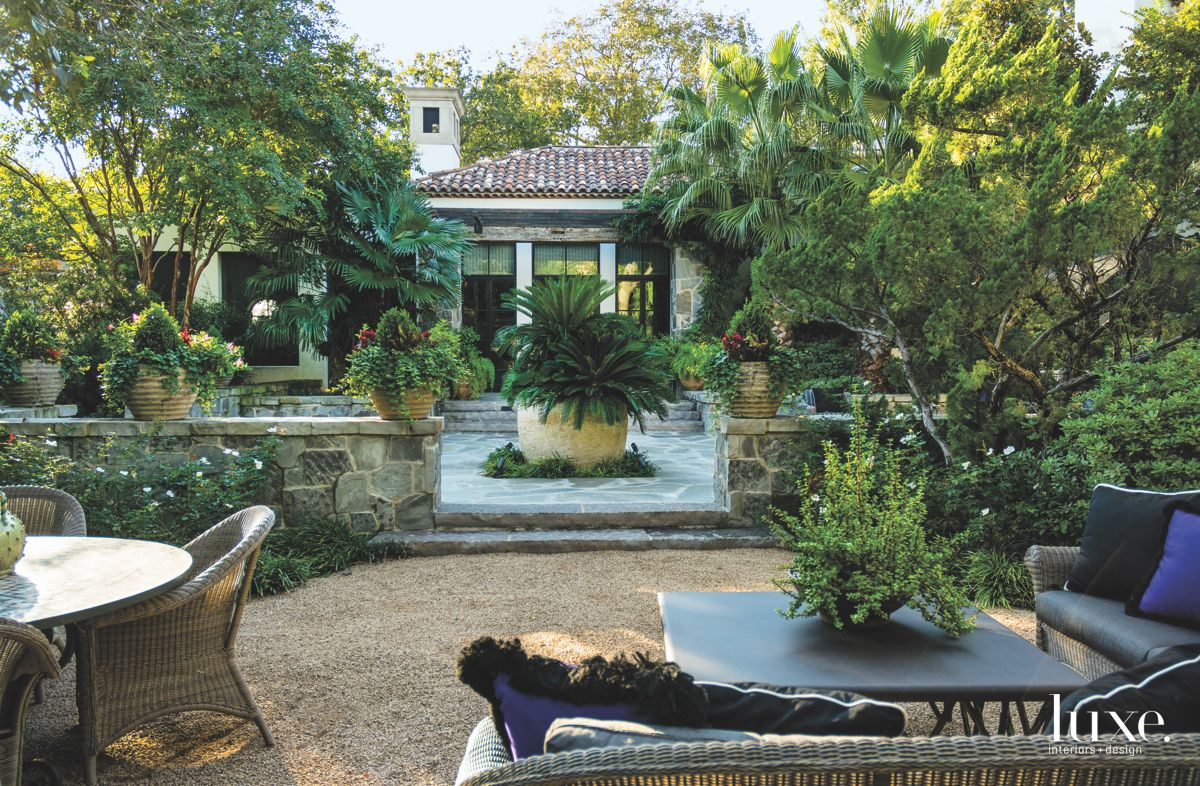 Outdoor Lush Garden with Wicker Outdoor Furniture and Stone Wall