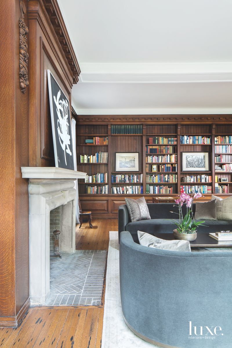 Brown Wooden Library with Stone Fireplace Artwork and Velvet Furniture