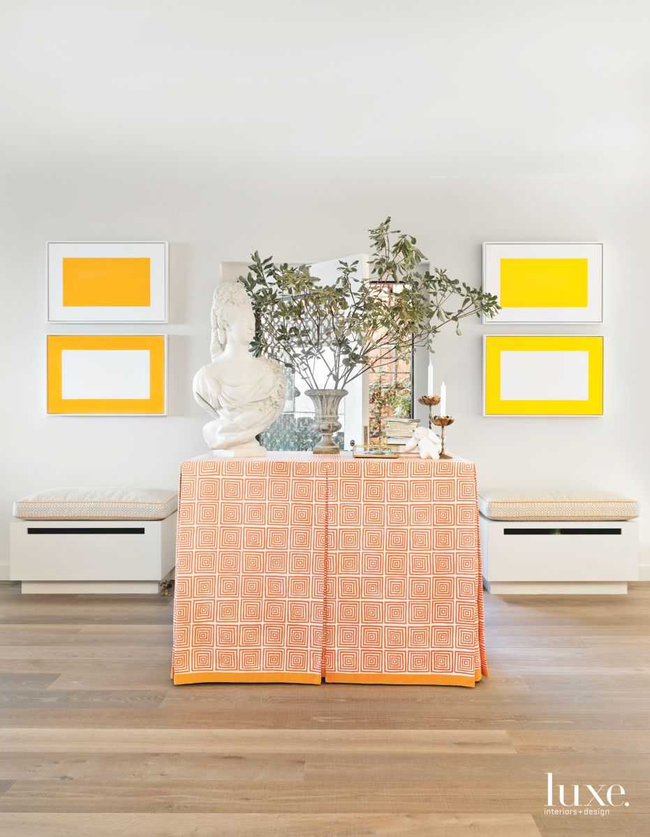 Bright Yellow Artwork and Matching Ottomans with Orange Tablecloth
