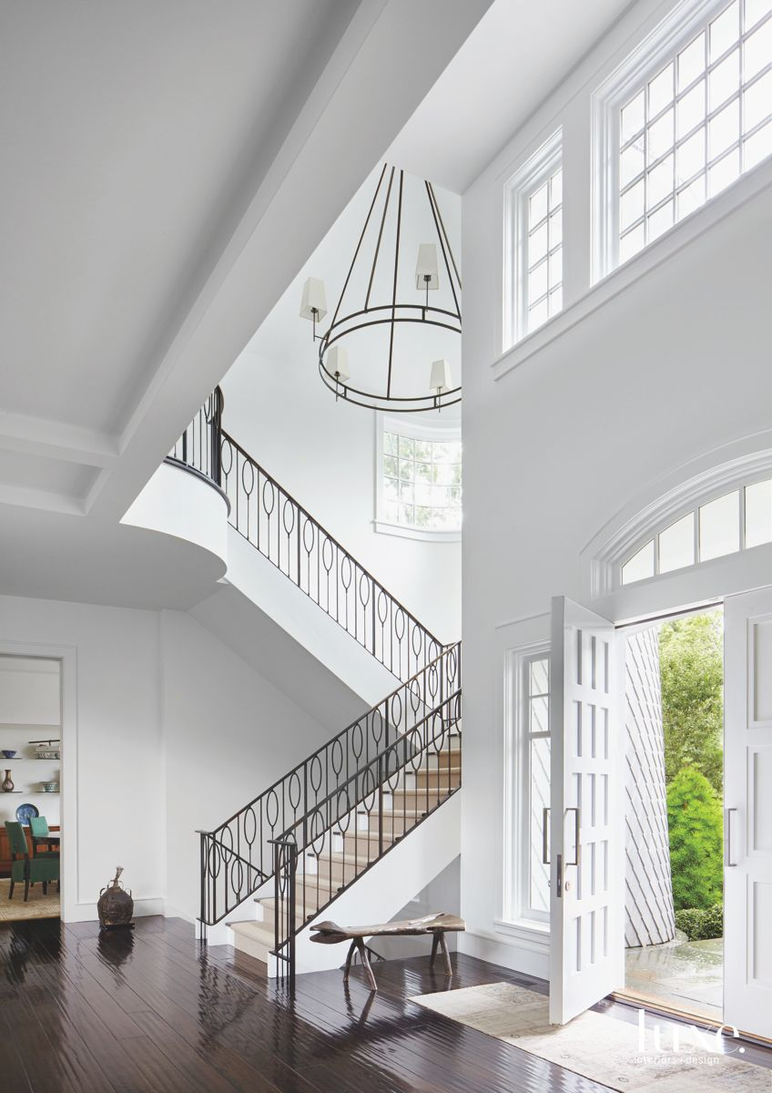 Contemporary Crisp White Entryway with Black Staircase Railing with High Ceilings and Chandelier