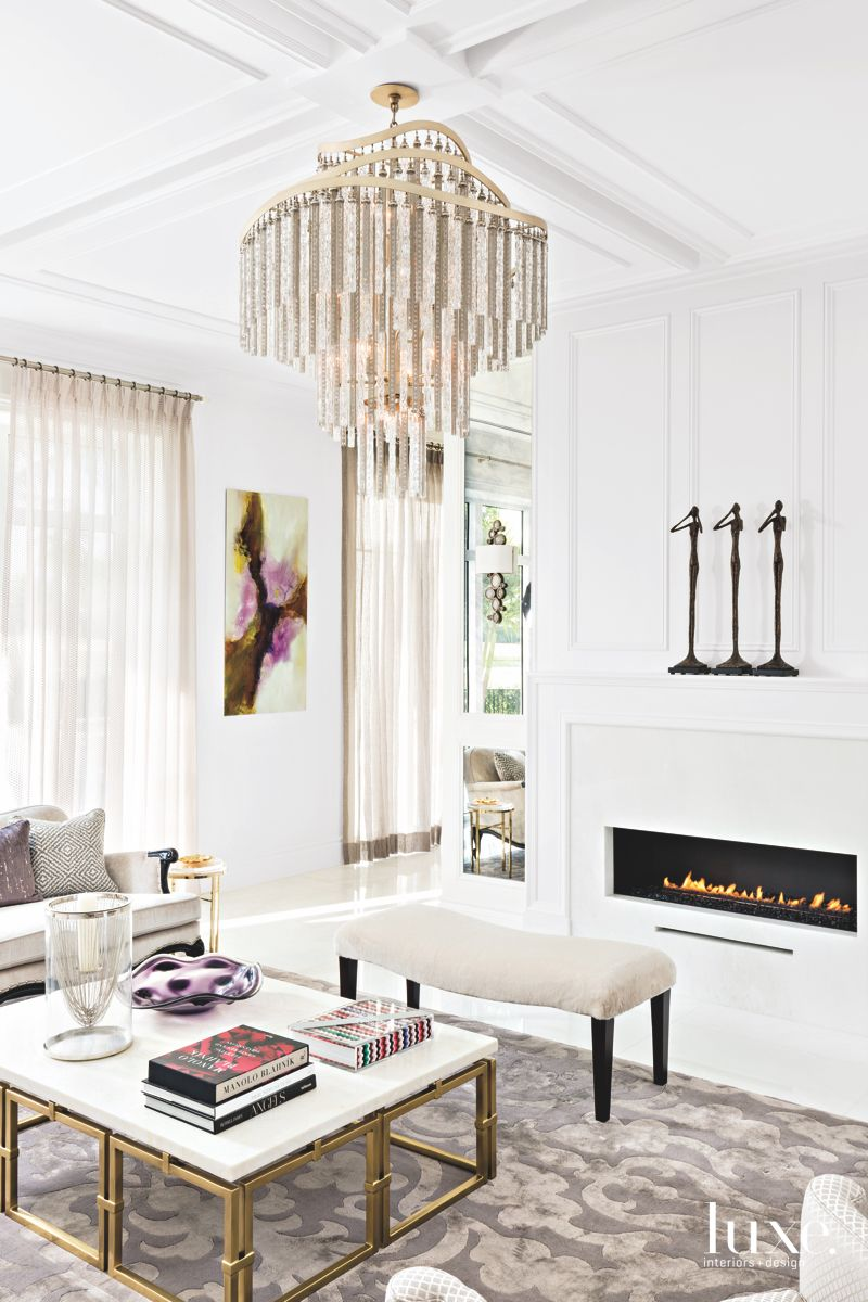 White Living Room with Glamorous Gold Fireplace and Chandelier