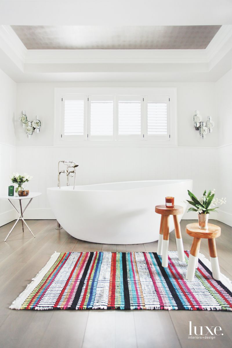 Large White Soaking Tub Master Bathroom with Colorful Striped Rug and Stools