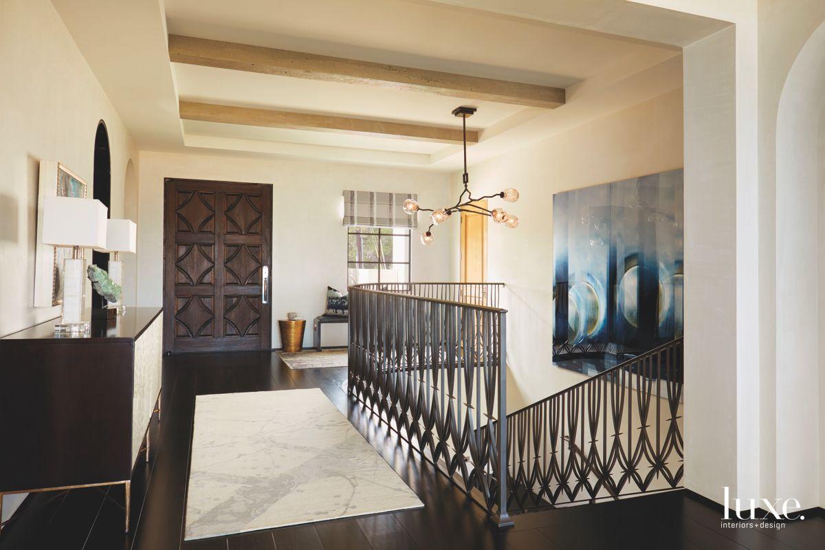 Dark Metal Railing Patterned Stairway with Dark Wood Doors and Commissioned Artwork