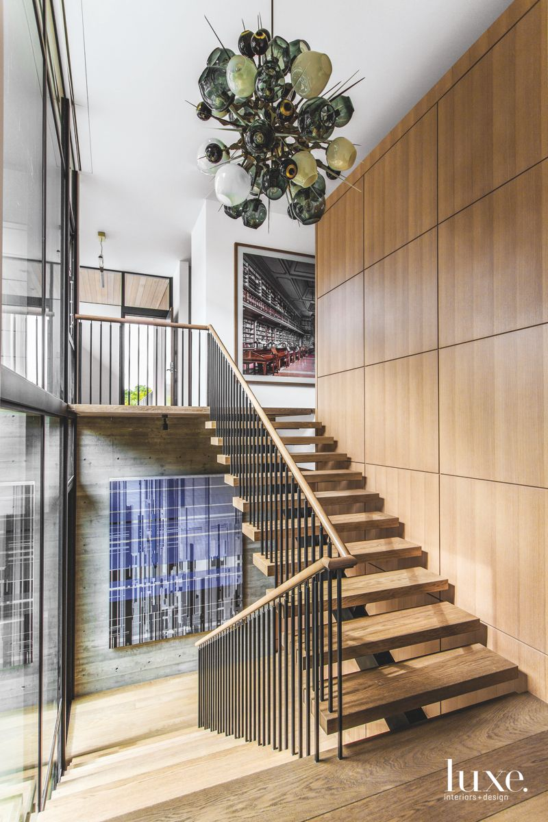 Pendant Entryway with Wooden Stairs and Art