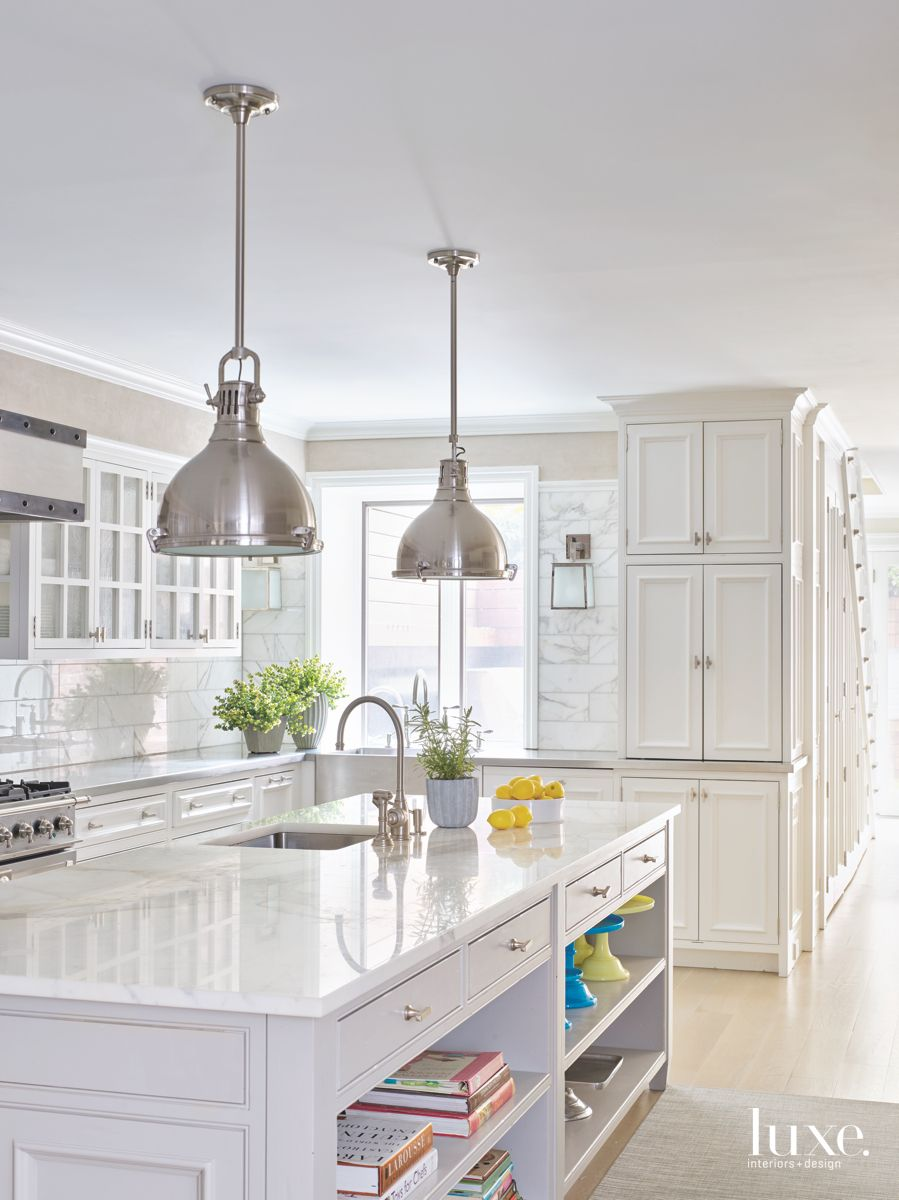 Completely White Kitchen With Chrome Pendant Lighting and Book Shelf Storage