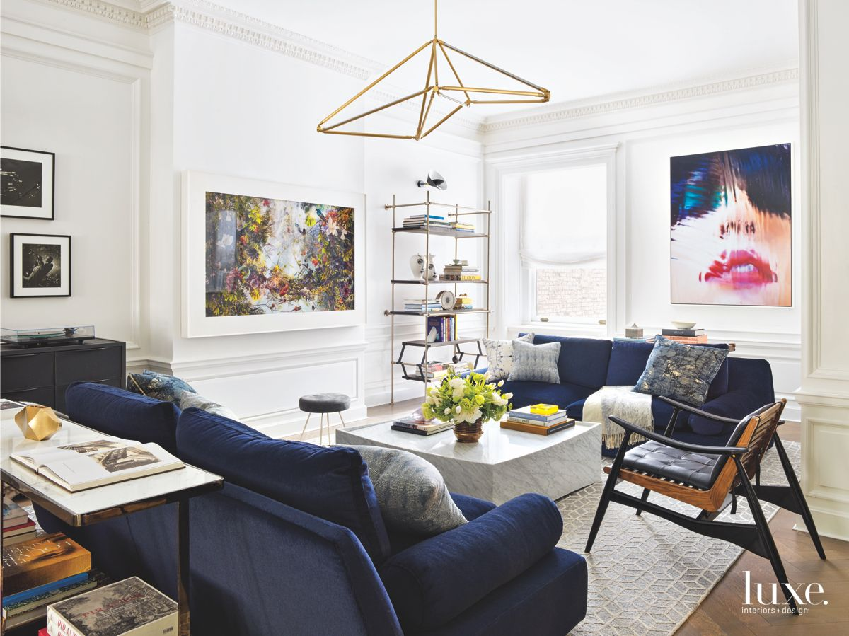 Artwork and Chandelier Parlor Room With Royal Blue Sofas Marble Island and Crown Moulding