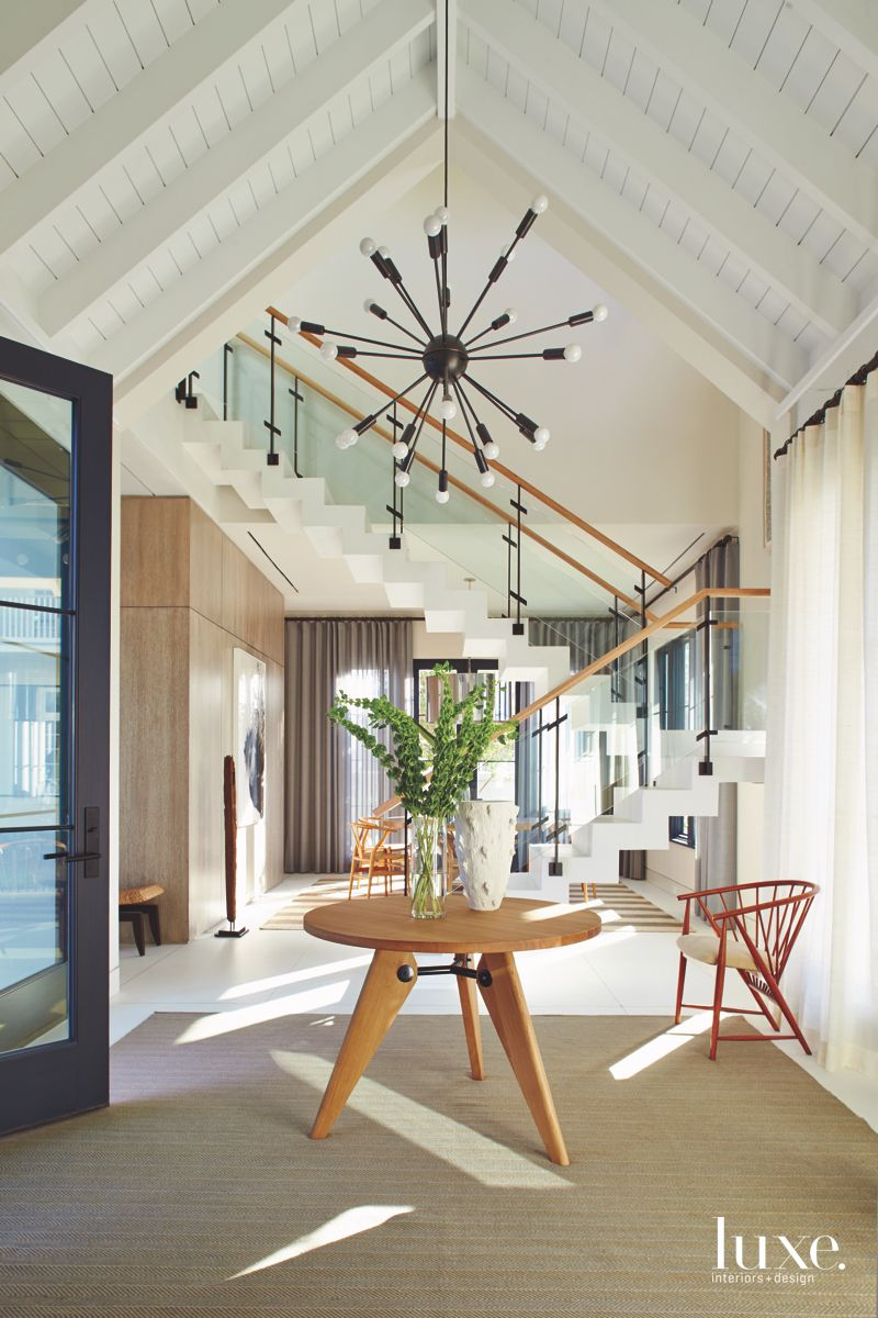 Vaulted Roof White Ceiling with Contemporary Staircase and Plants on Entry Table