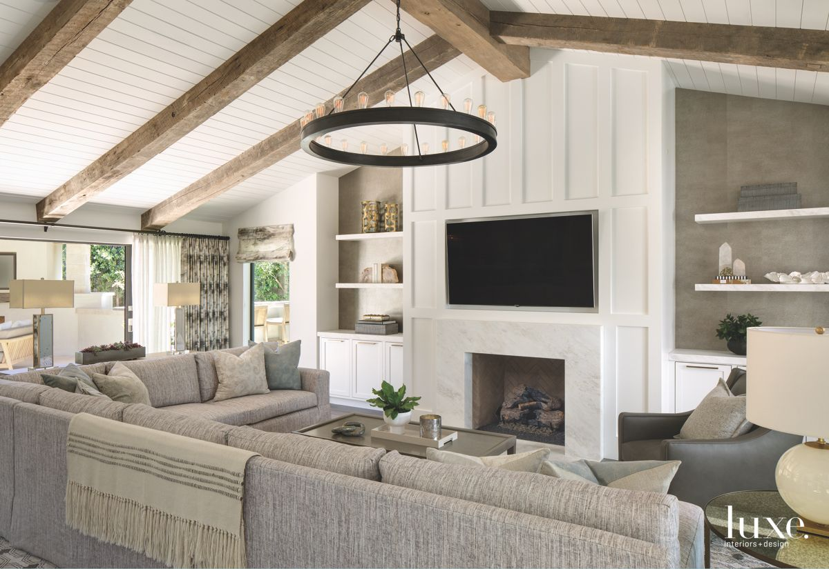 Reclaimed Wood Vaulted Ceiling Living Room with TV Over Fireplace and Neutral Couch