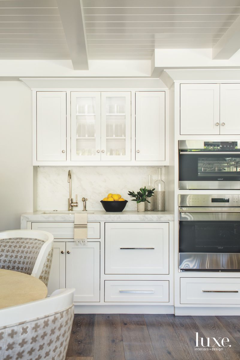 All White Kitchen Cabinets with Double Ovens and Shiny Hardware