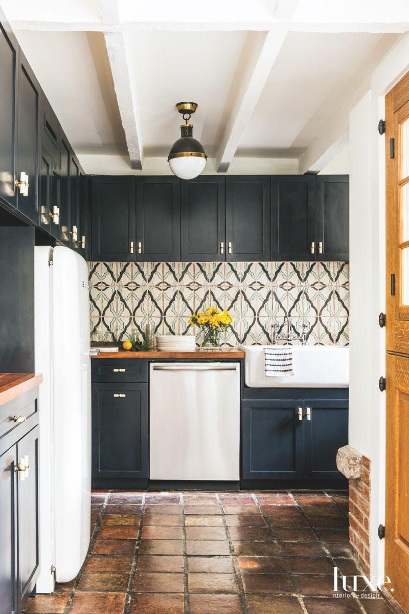 Original Stone Brick Flooring Kitchen with Organic Backsplash and Black Cabinets