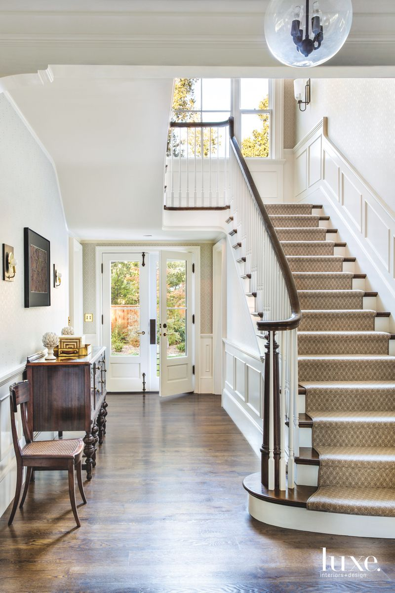 White Foyer with Antique Pieces and Staircase