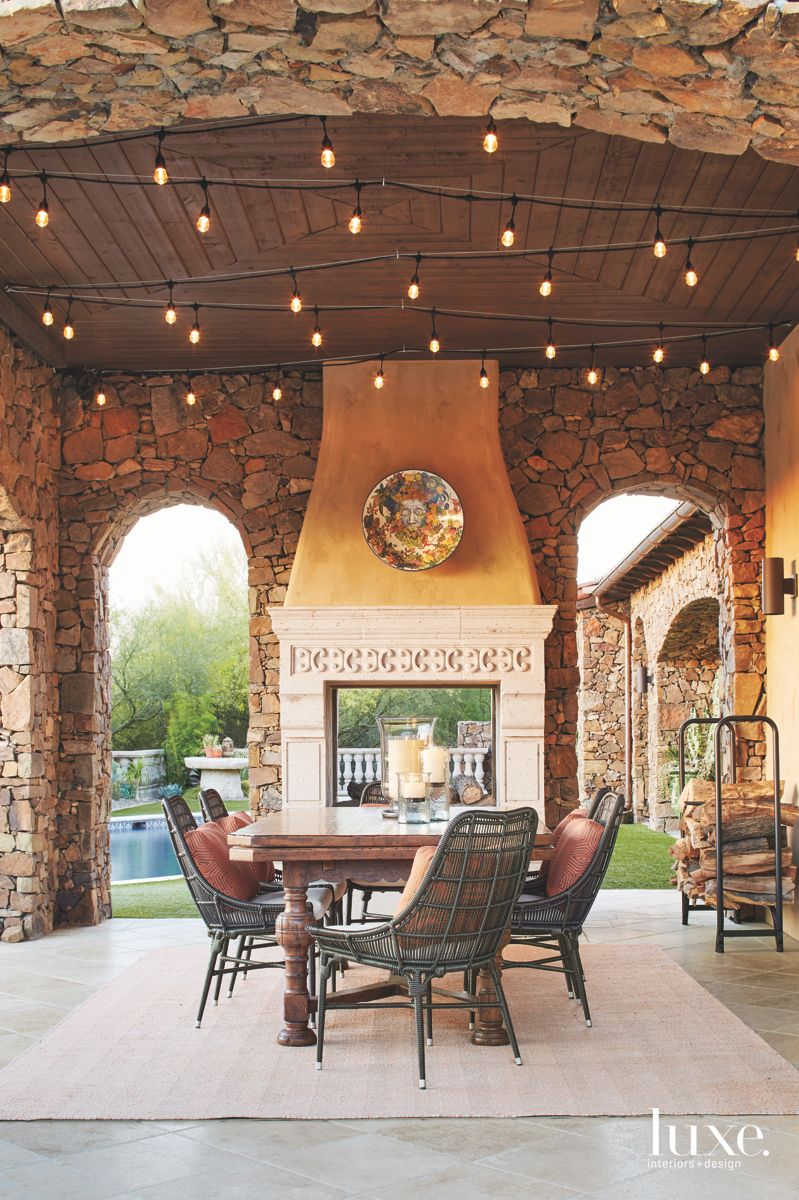 Stone Fireplace Outdoor Patio with Curved Chairs and Glass Encased Candles