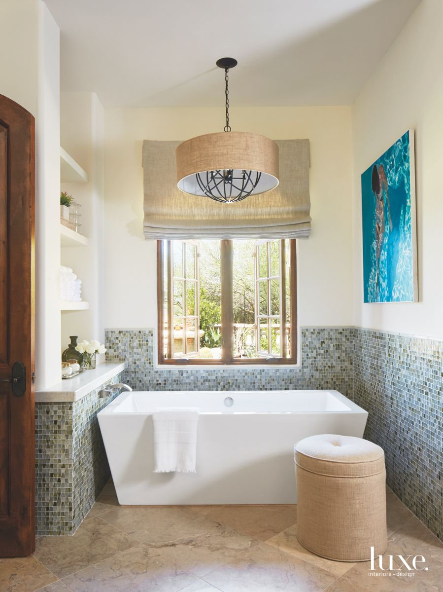 Wainscot Style Mosaic Tile Master Bathroom with Blue Artwork and Chandelier