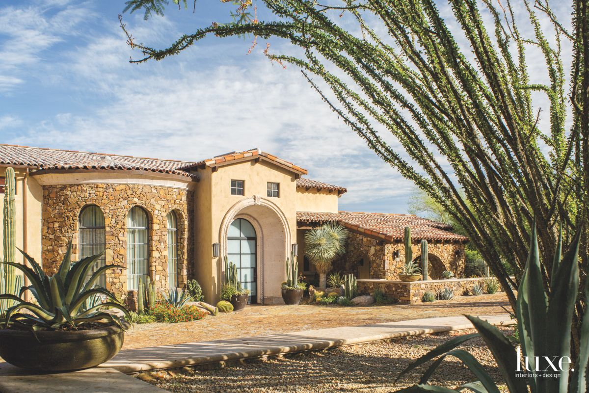 Arched Entry and Curved Wall Exterior with Cobblestone Driveway and Local Plants