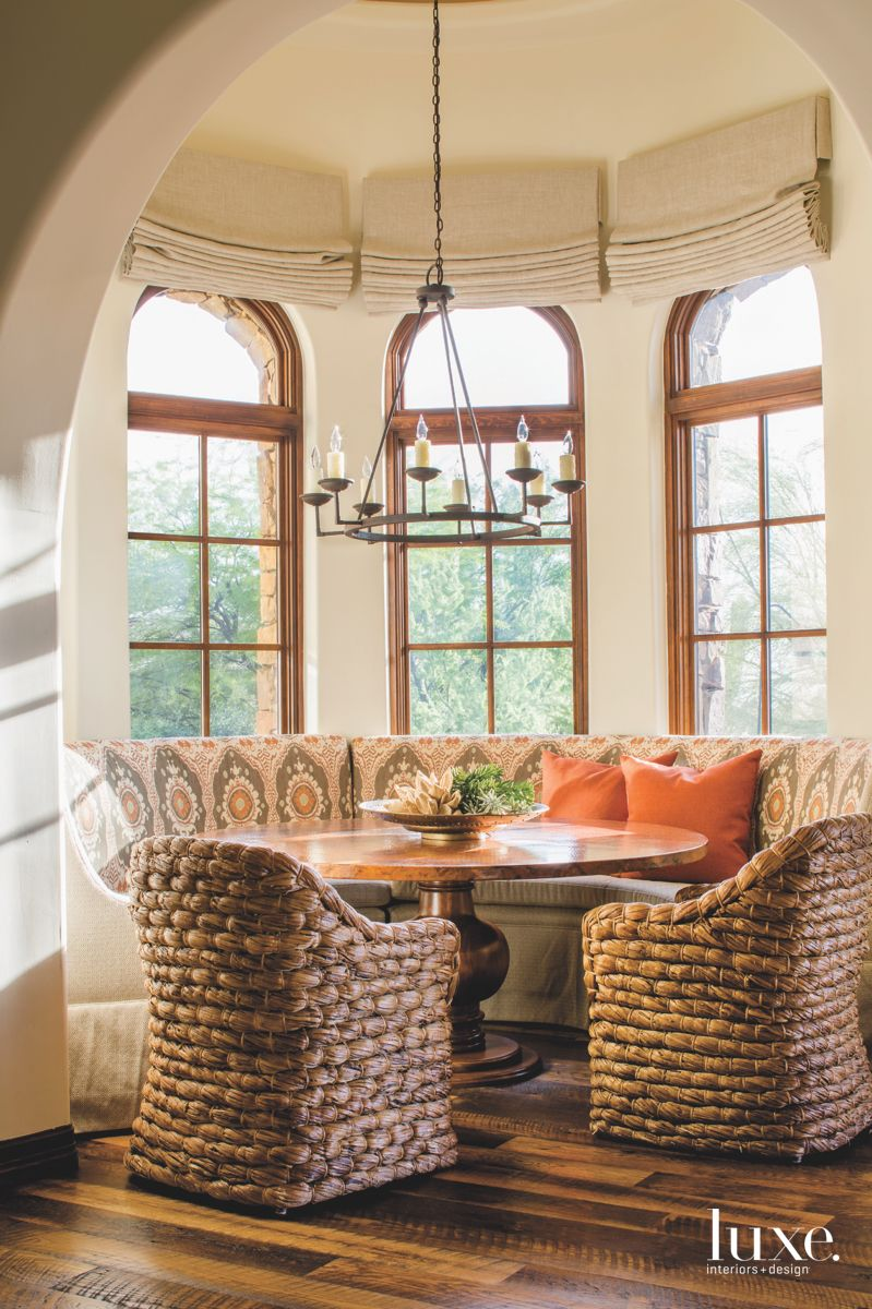 Wicker Chair Breakfast Nook with Arched Tall Windows and Orange Pillows