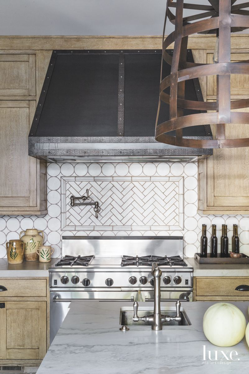 Subway Herringbone Tile Kitchen Backsplash with Dark Hood and Island Sink