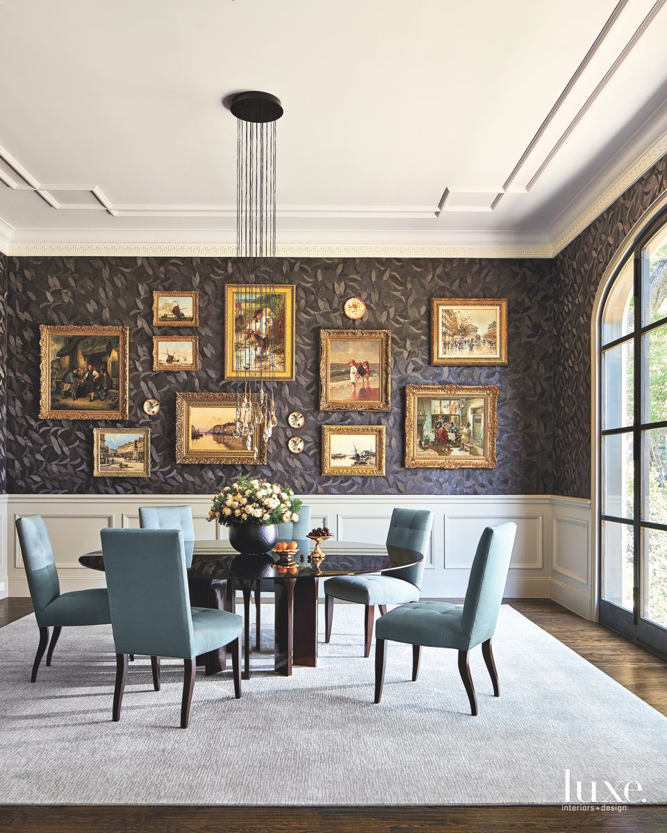 Dark Leaf Wallpaper Dining Room with Blue Chairs and Gallery Art Wall