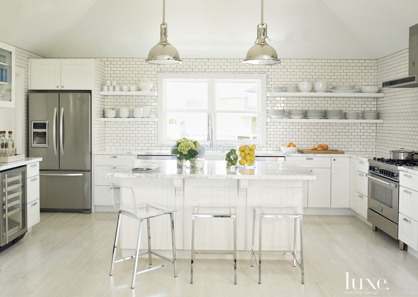 Contemporary White Kitchen with White Subway Tile Backsplash and Lucite Chairs