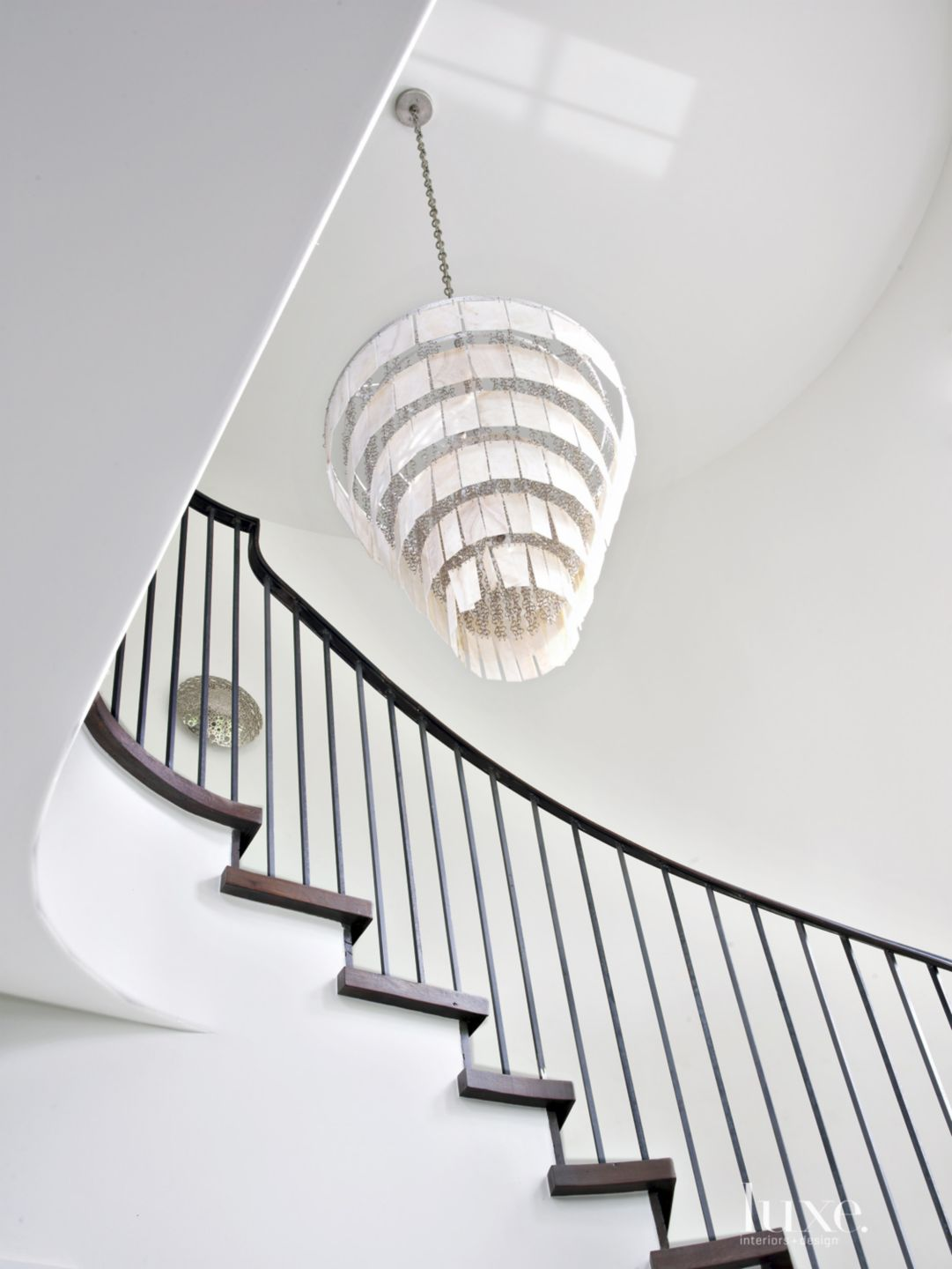 Transitional White Staircase with Spiraling Agate Chandelier