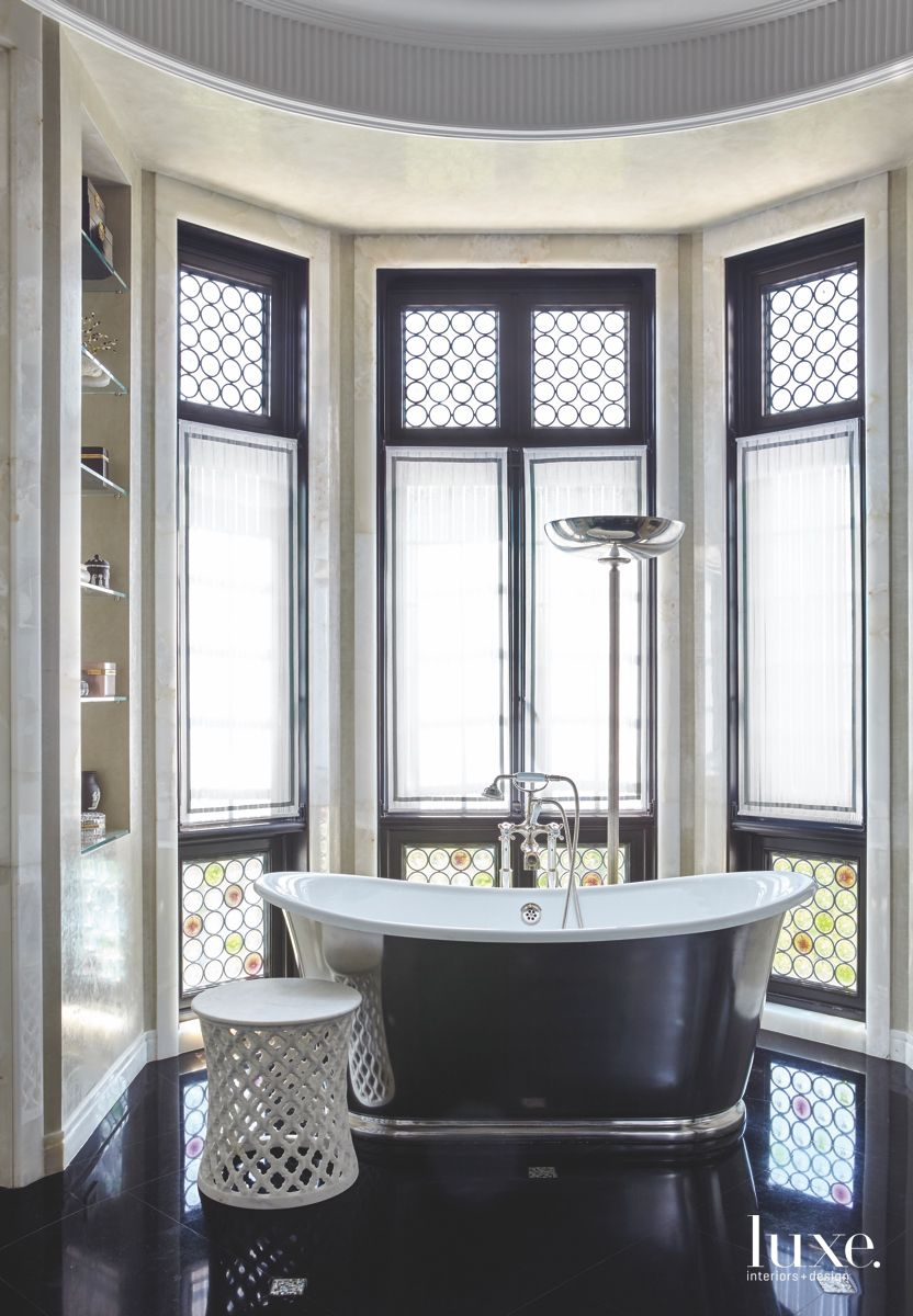 Shiny Black Master Bathroom with Large Soaking Tub and Decorative Table