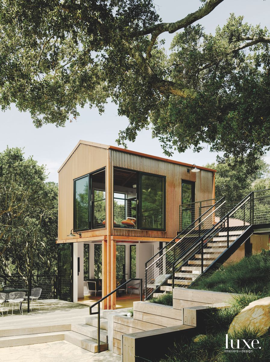 Contemporary Tree and Steel Siding Home on Stilts with Windows