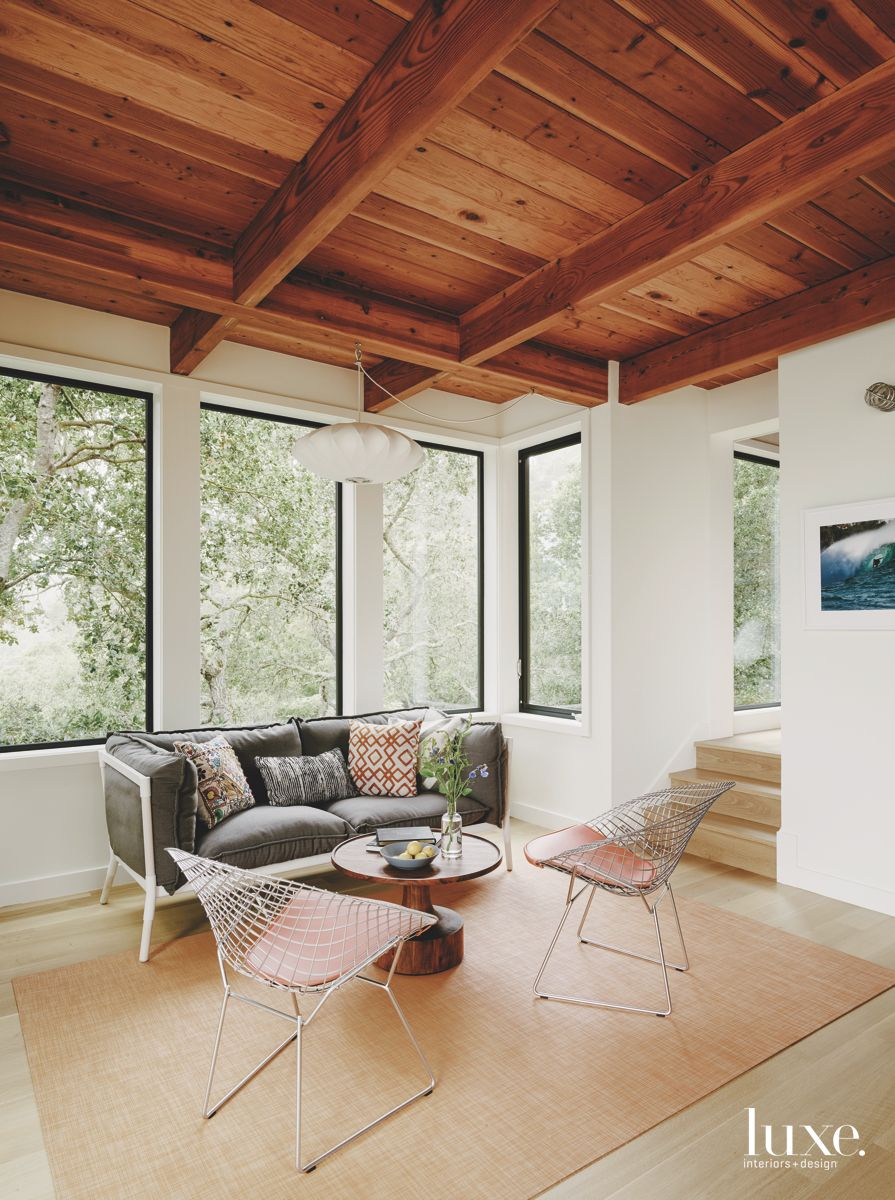 Wooden Beam Ceiling with Sofa and Modern Chairs and Artwork