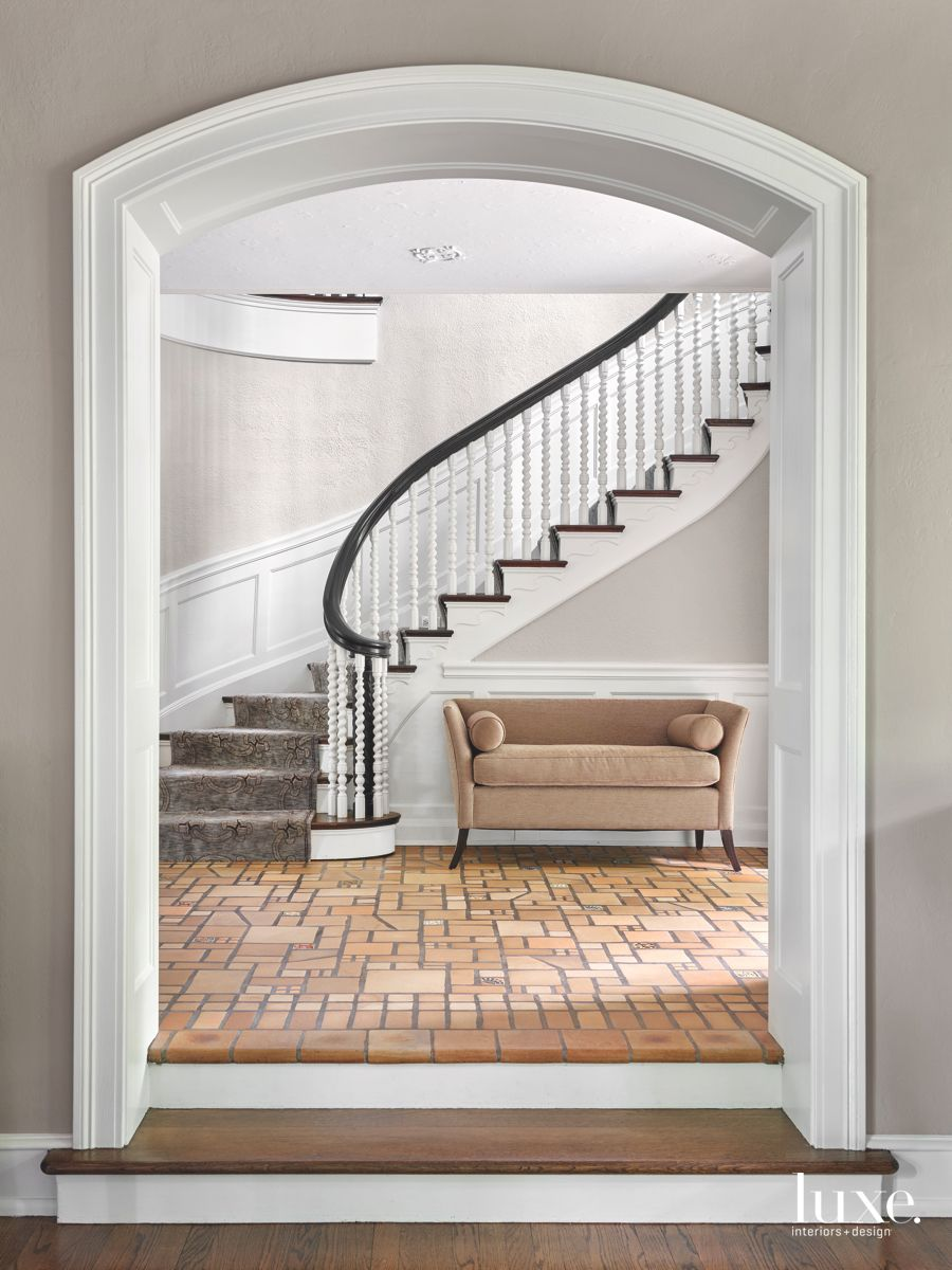 Arched Frame White Spiral Staircase with Neutral Stone and Bench