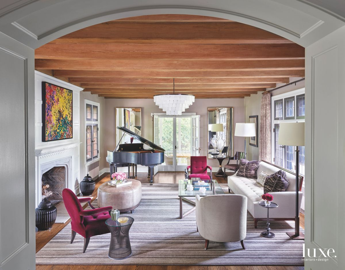 Beamed Ceiling Living Room with Fuchsia Velvet Chairs Fireplace Piano and Patterned Pillows