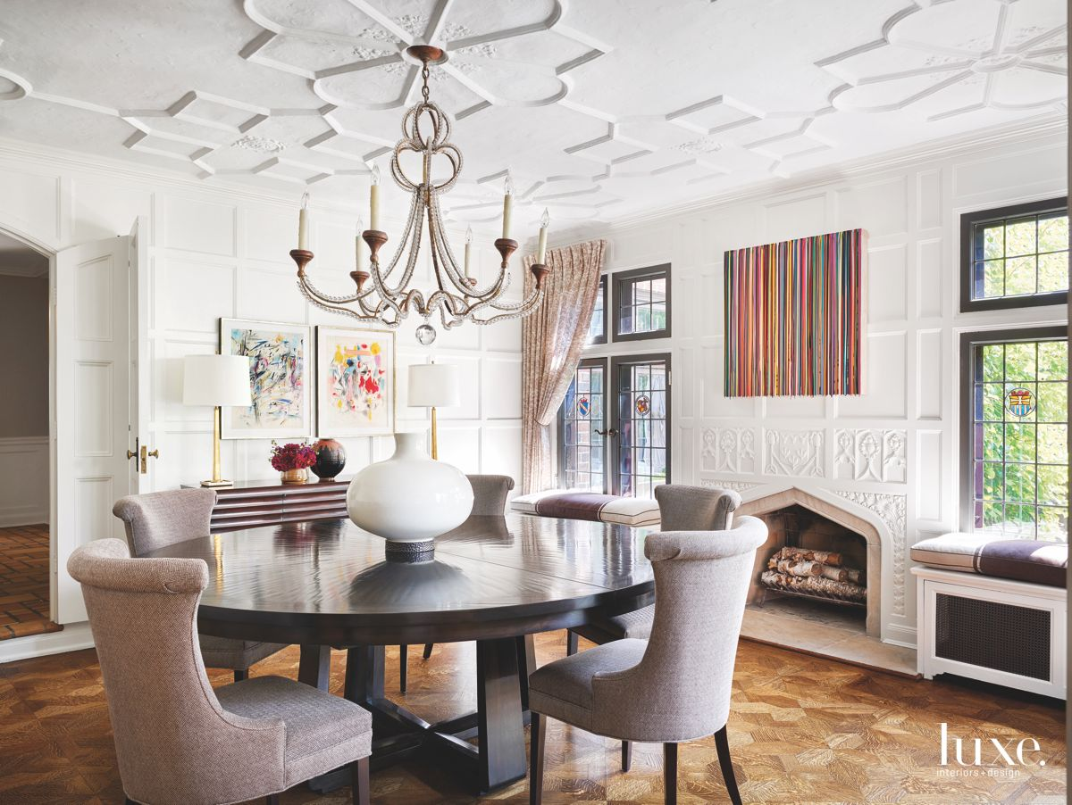 Detailed White Ceiling Dining Room with Chandelier, Artwork Ornate Fireplace and Window Benches