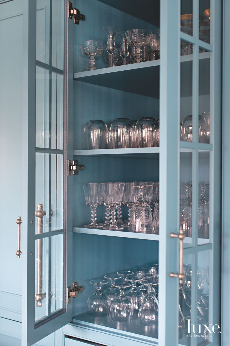 Blue Glass Front Cabinetry with Hardware Displayed for Glasses and Dishes