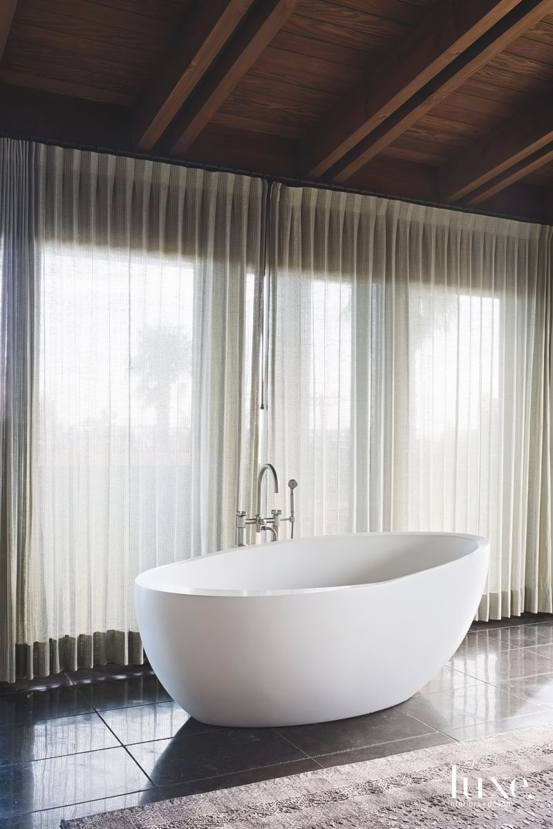 Large White Soaking Tub Master Bathroom with Draperies Covering the Windows
