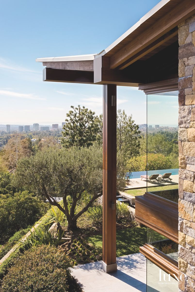 Cantilevered Roof View with Glass Corner and Stone Facade
