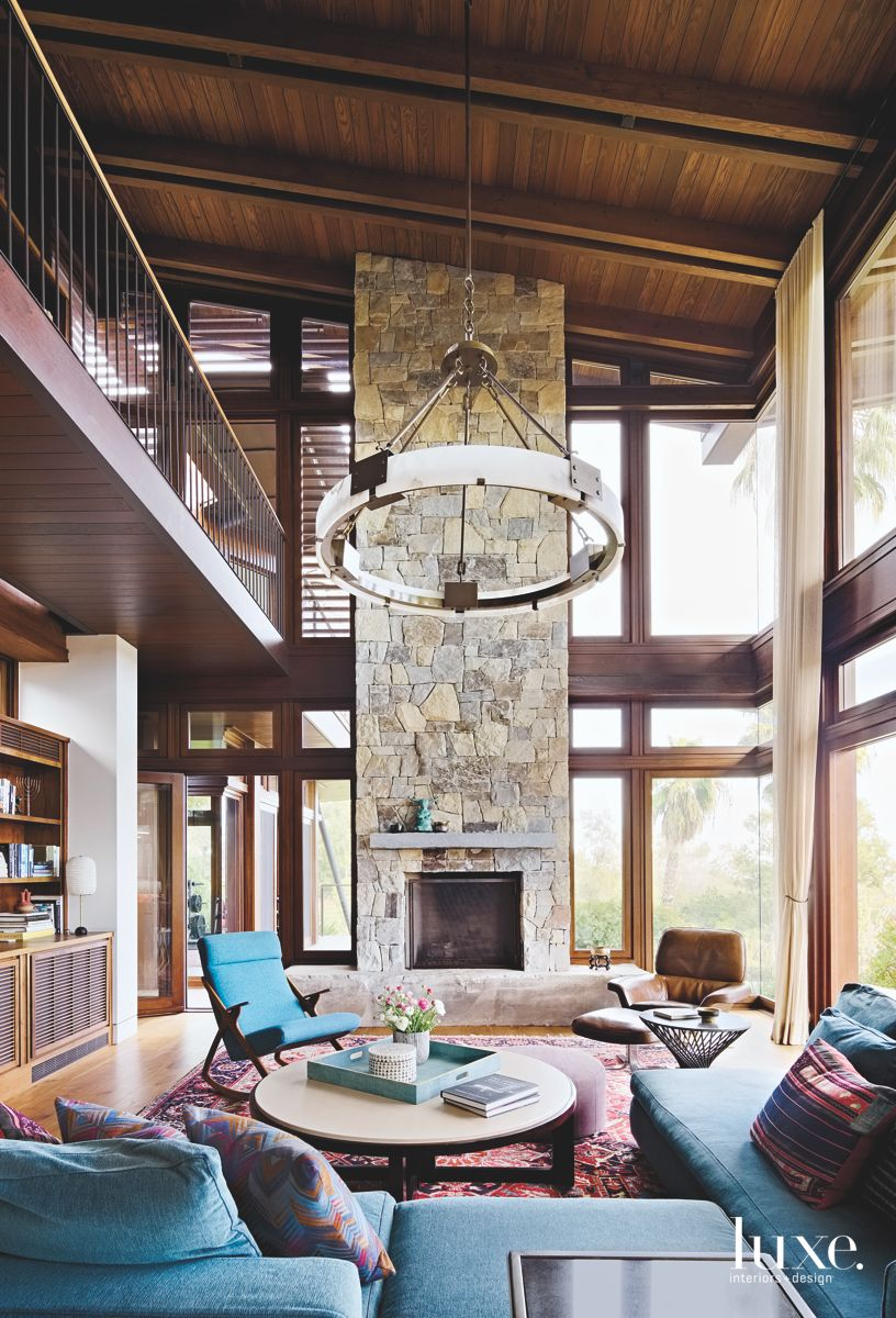 High Ceiling Stone Fireplace Great Room with Turquoise Furniture and Patterned Rug